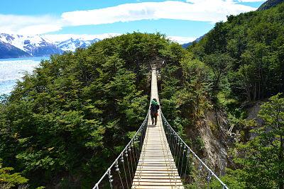 Imagen de un mohilero cruzando un puente colgante